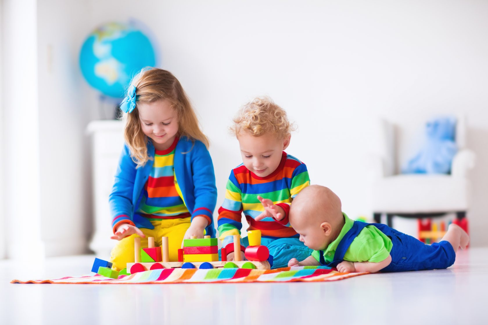 Children playing with wooden train. Toddler kid and baby play with blocks, trains and cars. Educational toys for preschool and kindergarten child. Boy and girl build toy railroad at home or daycare.